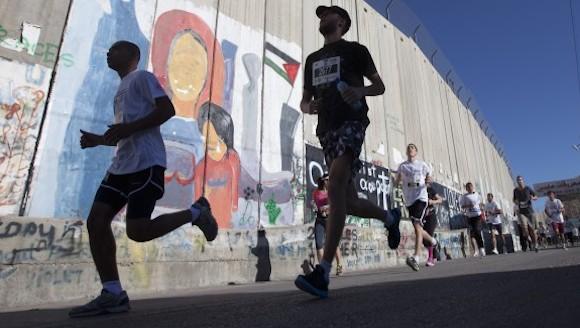 Palestinos y extranjeros, incluyendo activistas por la paz, corriendo en la ruta a lo largo del Muro de Separación en el Segundo Maratón Internacional Palestino, en la ciudad de Belén. Participaron unos mil corredores. israel prohibió el acceso de unos 30 participantes, incluyendo un atleta olímpico. AP Photo/Majdi Mohammed
