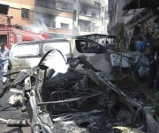 People gather at the site of two car bomb attacks at al-Abassia roundabout in Homs