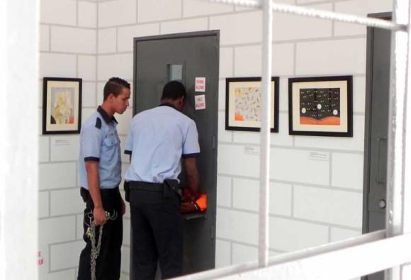 Acción perfomática del momento en que son encadenados antes de salir de la celda para el traslado de los prisioneros hacia su visita con los abogados.