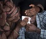 Bizimana Emmanuel, quien nació dos años antes del genocidido en Ruanda de 1994, es consolado por una mujer no identificada, mientras atendían una ceremonia pública por el 20 aniversario de aquel genocidio que duró cien días, en el estadio Amahoro, en Kigali, Ruanda, Abril 7 de 2014. AP Photo/Ben Curtis