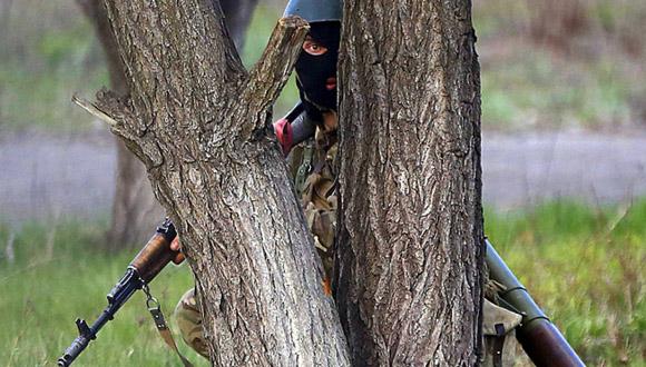 Soldado ucraniano oculto detrás de un árbol en Kramatorsk. Foto: Reuters.