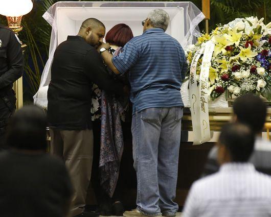 La familia de 'Cheo' Feliciano junto al cuerpo del fallecido artista. Foto: EFE