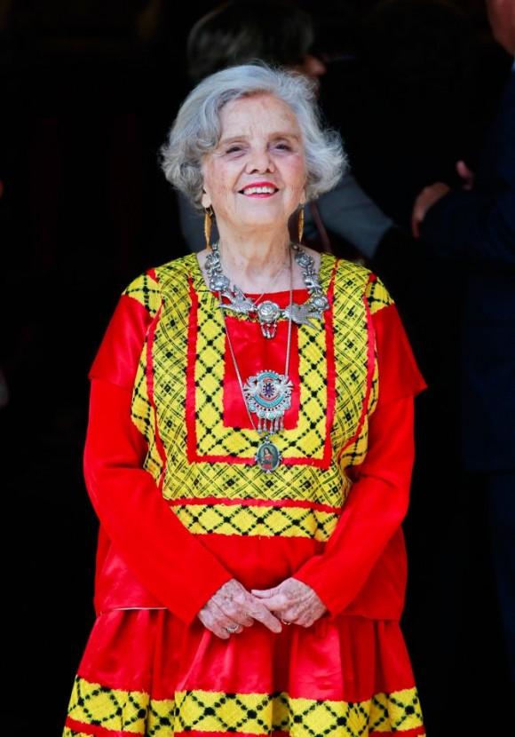 Elena Poniatowska posa para la prensa a su llegada al paraninfo de la Universidad de Alcalá de Henares. La escritora llevaba un traje rojo y dorado, regalo de las mujeres de Juchitán, un collar de plata y pendientes con forma de pez en oro.