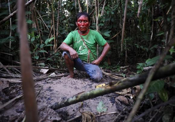 Un Ashaninka llamado Uarenco se arrodilla sobre la tumba de su sobrina. Su familia fue enterrada a lo largo de la orilla del Envira dos semanas antes. Murió mientras navegaban el río en busca de atención médica.