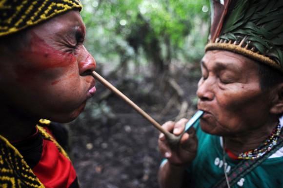 Un líder espiritual de los Huni Kui sopla un polvo herbal dentro de la nariz de uno de los miembros de la tribu durante una ceremonia.