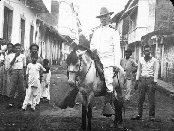 Capitán Dennis Geary de la artillería pesada de California monta su caballo a través de Cavite en Filipinas
