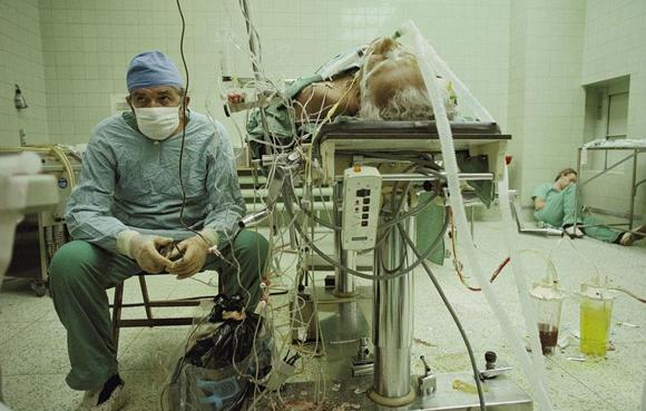 Cirujano del corazón después una operación de transplante de corazón que duró 23 horas, su asistente está en el suelo en un rincón