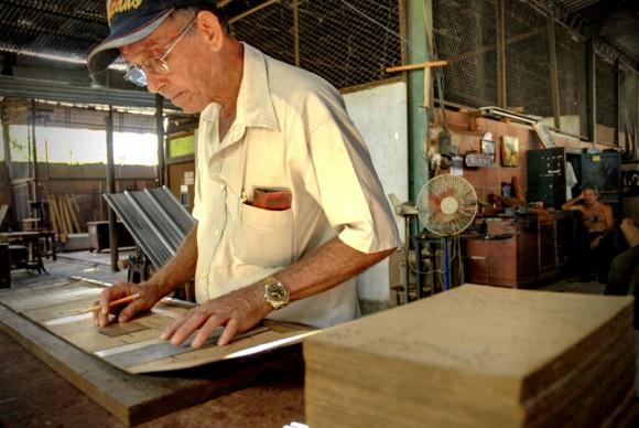 Porfirio Sánchez Hernández transcribe la partitura musical al cartón, libro o pieza musical que utiliza el órgano neumático, en la Fábrica de Instrumentos Musicales y Órganos Neumáticos, única de su tipo en Cuba, ubicada en la oriental ciudad de Holguín. FOTO/Juan Pablo Carreras