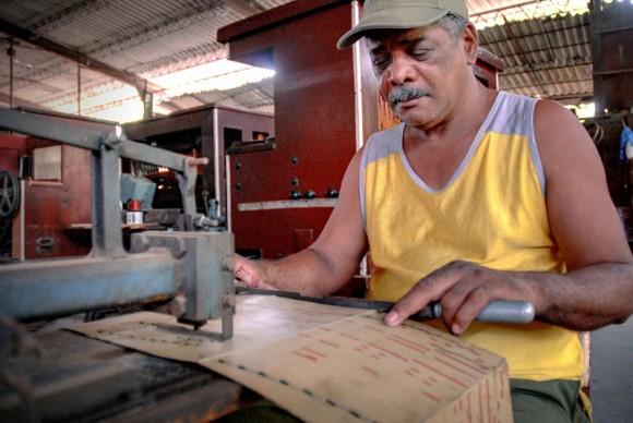 Arnoldo Álvarez Zaldívar alista el libro o pieza musical que utiliza el órgano neumático, en la máquina perforadora de notas musicales, de la Fábrica de Instrumentos Musicales y Órganos Neumáticos, única de su tipo en Cuba, ubicada en la oriental ciudad de Holguín. FOTO/Juan Pablo Carreras