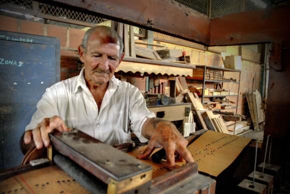 Francisco Cuayo, proveniente de familia precursora de la tradición de órganos musicales, comprueba el buen funcionamiento de uno de los instrumentos, en la Fábrica de Instrumentos Musicales y Órganos Neumáticos, única de su tipo en Cuba, ubicada en la oriental ciudad de Holguín. FOTO/Juan Pablo Carreras