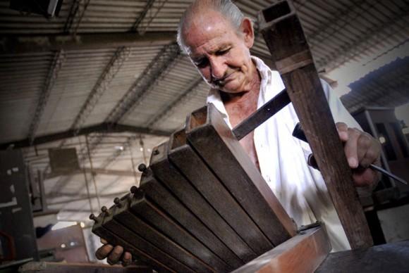 Francisco Cuayo, proveniente de una familia precursora de la tradición de órganos musicales y fundador del taller, da mantenimiento a una escala de acompañamiento en la Fábrica de Instrumentos Musicales y Órganos Neumáticos, única de su tipo en Cuba, ubicada en la oriental ciudad de Holguín. FOTO/Juan Pablo Carreras