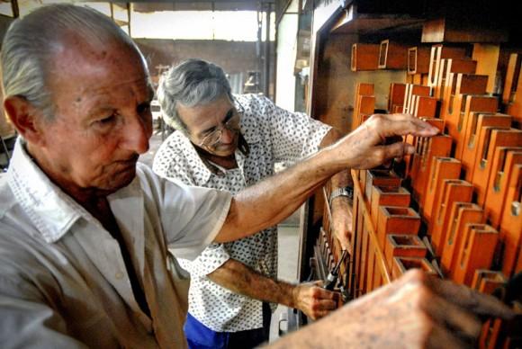 Francisco Cuayo, proveniente de familia precursora de la tradición de órganos musicales y Antonio Enrique Fernández (C), ajustan una escala de acompañamiento, en la Fábrica de Instrumentos Musicales y Órganos Neumáticos, única de su tipo en Cuba, ubicada en la oriental ciudad de Holguín. FOTO/Juan Pablo Carreras