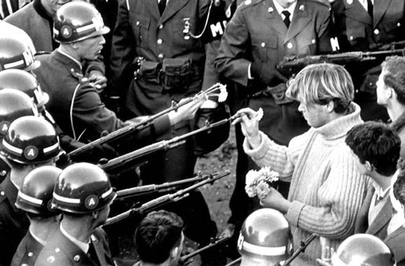 Los protestantes colocan flores en las escopetas de los agentes de policía