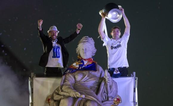 Los capitanes del Real Madrid Iker Casillas (d) y Sergio Ramos (i) ofrecen la copa a los aficionados junto a la estatua de la Cibeles, en Madrid, tras vencer anoche al Atlético de Madrid en la final de la Liga de Campeones disputada en Lisboa. Paul White (AP)