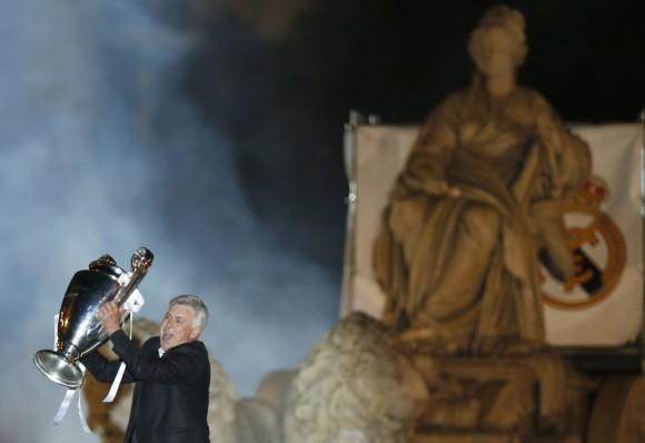 El entrenador del Real Madrid, Carlo Ancelotti, ofrece el trofeo a los seguidores desde lo alto de la pasarela instalada alrededor de la estatua de la diosa Cibeles. Andrea Comas (Reuters)