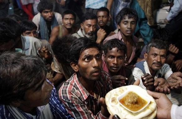 Un sin techo indio espera ansioso un poco de comida que dan en un comedor social a las afueras de Nueva Delhi, India
