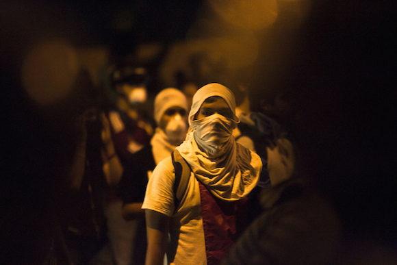 Jóvenes encapuchados participan en una manifestación frente a un cordón policial hoy, domingo 16 de febrero de 2014, en Caracas (Venezuela). Cientos de personas se concentraron pacíficamente hoy en el este de la capital venezolana para continuar con las manifestaciones contra el Gobierno venezolano y para exigir la libertad de los de los detenidos en las marchas que se han desarrollado a lo largo de la semana. EFE/SANTI DONAIRE