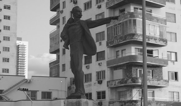 José Marti. Tribuna Antimperialista. Escultura de José Marti del artista habanero Andrés González. El Apóstol trae un niño en un brazo, mientras el otro, en gesto resuelto, permanece extendido, señalando hacia la Oficina de Intereses de Washington en la Habana, desde la Tribuna Antimperialista.