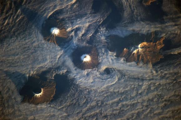 islas de las cuatro montañas se ofrecen en esta imagen fotografiada por un miembro de la tripulación Expedición 38 de la ISS el 15 de noviembre de 2013. Mañana luz del sol ilumina las pistas de orientación al sureste de las islas de la fotografía. Las islas, parte de la cadena de las islas Aleutianas , en realidad son las laderas superiores de los volcanes se elevan desde el fondo del mar ; Carlisle , Cleveland, Herbert , y Tana . (NASA )