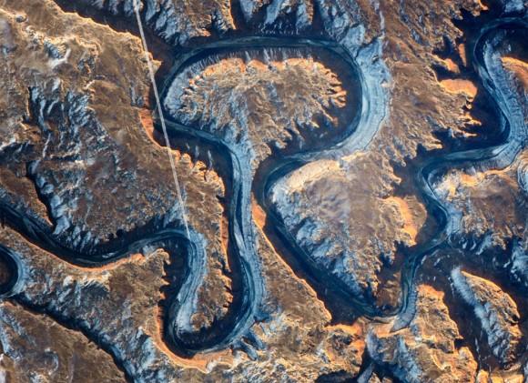 Este sector del cañón del Río Verde en el este de Utah se conoce como Curva del Bowknot debido a la forma en que el río se dobla sobre sí mismo. En esta fotografía tomada por un astronauta en la Estación Espacial Internacional el 22 de enero de 2014, el Green River aparece oscuro debido a que se encuentra en la sombra, 300 m (1.000 pies) por debajo del paisaje circundante. Los acantilados de color amarillo con tintes tamizados por la salida del sol dan una idea de las paredes empinadas del cañón. La línea blanca recta a través de la escena es la estela de un jet liner volando sobre el cañón. Foto: NASA.