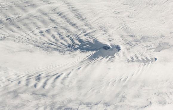 Esta imagen de campo amplio de visión fotografiada por un miembro de la tripulación Expedición 38 de la ISS muestra una franja de este a oeste del océano Índico suroccidental , el 28 de enero de 2014. Dos islas remotas, parte del sur de Francia y Tierras antárticas , aparecen en el centro de la imagen . Isla Posesión (centro derecha ) y la isla del este (centro ) se encuentran a sólo 18 kilometros de largo. Una isla pequeña, Ile aux Cochons ( Pigs Island) , se encuentra a 100 kilómetros al oeste. Cada isla ha puesto en marcha los trenes en forma de V de las ondas , como las olas de proa , como el aire fluye a través de las islas del oeste (derecha a izquierda). Los patrones de las ondas de proa se superponen en la nube baja regional stratus ( manta ) que es tan común en el Océano Índico meridional , a 50 grados de latitud sur . Este punto de vista fue tomada desde más de 400 kilómetros por encima de la superficie del mar y revela las relaciones que no pudieran ser entendidos fácilmente por alguien de pie en una de las islas . Por ejemplo , las islas más grandes y más altos producen olas más grandes. Así que el mayor se están generando por la Isla Posesión ( 934 metros sobre el nivel del mar en el punto más alto), y de las islas del este , frente a las olas más pequeñas desarrolladas a favor del viento de la pequeña isla de Pingouins ( 340 metros sobre el nivel del mar alto, invisible debajo de la cubierta de nubes ) . (NASA )