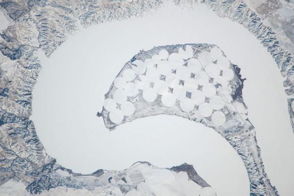 Lake Sharpe cerca de Lower Brule, Dakota del Sur se ofrecen en esta imagen fotografiada por un miembro de la tripulación Expedición 38 a bordo de la ISS el 26 de diciembre de 2013. El río Missouri, en algunos lugares, tiene muchas curvas serpenteantes como este , ocupado por el lago Sharpe, un aproximado de 130 kilómetros ( 80 millas ) de largo embalse formado detrás de la curva grande presa . La superficie del lago está congelado y cubierto de nieve , lo que también pone de relieve los campos agrícolas circulares en la pequeña península dentro de la curva de meandro. Este tipo de campo indica el riego de pivote central , donde el agua se distribuye desde un punto central radialmente hacia fuera utilizando rociadores para cubrir el área del campo . (NASA )