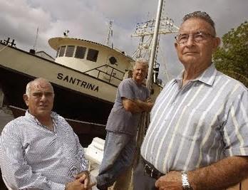 De izquierda a derecha, los terroristas Santiago Alvarez, Osvaldo Mitat y José Hilario Pujol junto al barco Santrina, que introdujo de manera ileagal a Posada Carriles en los Estados Unidos, en el 2005. (Roberto Koltun/ El Nuevo Herald).