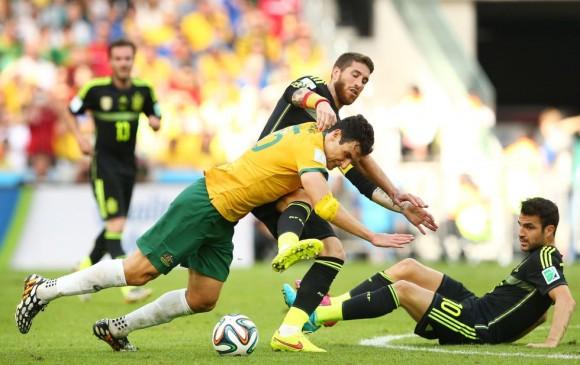 Mile Jedinak de Australia pelea por el balón con Sergio Ramos ante la mirada de Cesc Fábregas en el suelo. QUINN ROONEY (GETTY IMAGES)