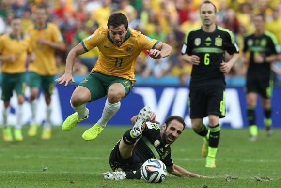 Tommy Oar salta para esquivar a JuanFran (en el suelo) en su carrera por el balón ante la mirada de Iniesta. ALEJANDRO RUESGA