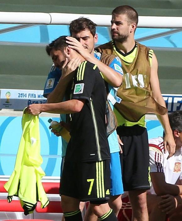 Iker Casillas consuela a David Villa, que se incorpora al banquillo tras haber sido sustituido por Juan Mata. ALEJANDRO RUESGA (EL PAÍS)