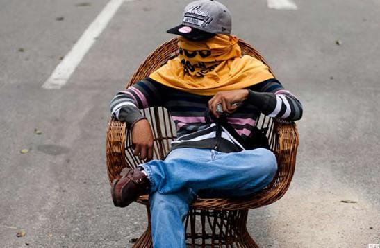 Un guarimbero descansa en un cierre de calles en Caracas, en febrero de 2014. Foto: Eco Popular.