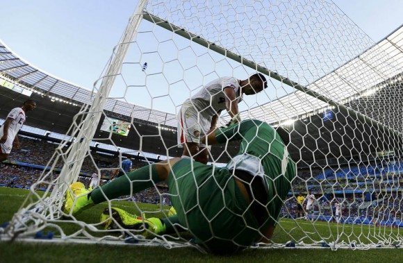 Costa Rica's Navas is helped out of his goal by Umana after making a save against Uruguay during their 2014 World Cup Group D soccer match at the Castelao stadium in Fortaleza