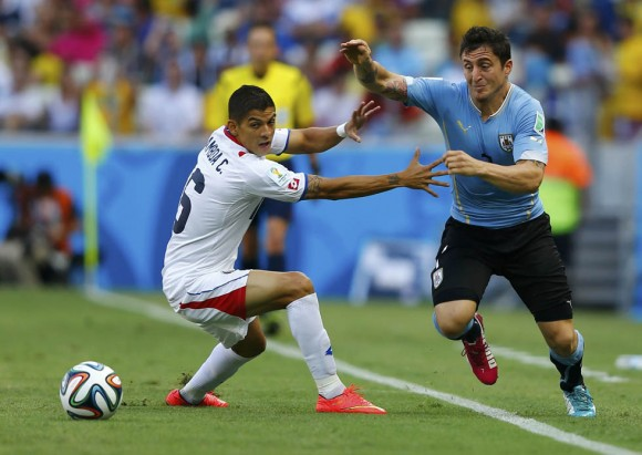 Costa Rica's Gamboa and Uruguay's Rodriguez fight for the ball during 2014 World Cup soccer match in Fortaleza