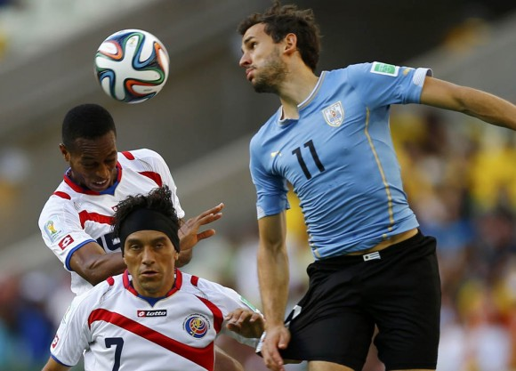 Costa Rica's Junior Diaz and Christian Bolanos fight for the ball against Uruguay's Christian Stuani during their 2014 World Cup Group D soccer match at the Castelao arena in Fortaleza