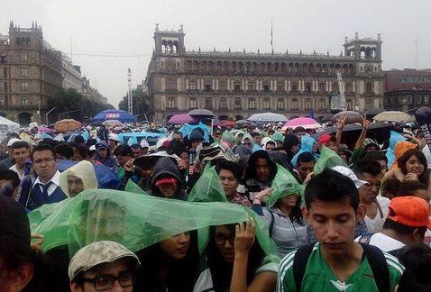 Aficionados resisten la lluvia y continúan en el Zócalo viendo el partido del Tri ante Croacia.