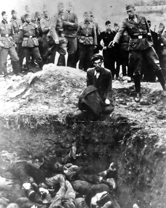 """Imagen sacada del álbum personal de un soldado de Einsatzgruppen (Conjunto de escuadrones de ejecución itinerantes especiales formados por miembros de las SS, SD y otros miembros de la policía secreta de la Alemania Nazi) etiquetada en la parte de atrás como """"El último judío de Vinnytsia"""". Muestra como un miembro de Einsatzgruppe D está a punto de dispararle a un hombre judío que se encuentra arrodillado frente a una fosa común en Vinnytsia, Ucrania, en 1941. Todos los 28,000 judíos de Vinnytsia y sus alrededores fueron masacrados en esa época."""