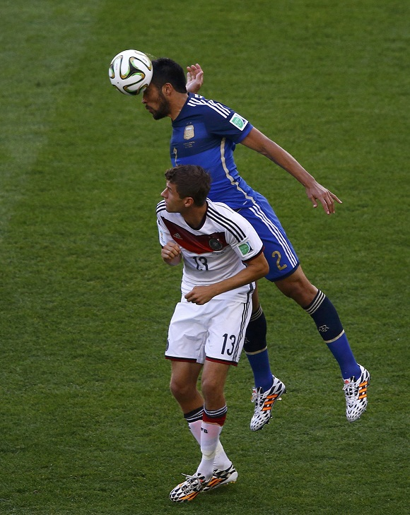 Germany's Mueller and Argentina's Garay fight for the ball during their 2014 World Cup final at the Maracana stadium in Rio de Janeiro