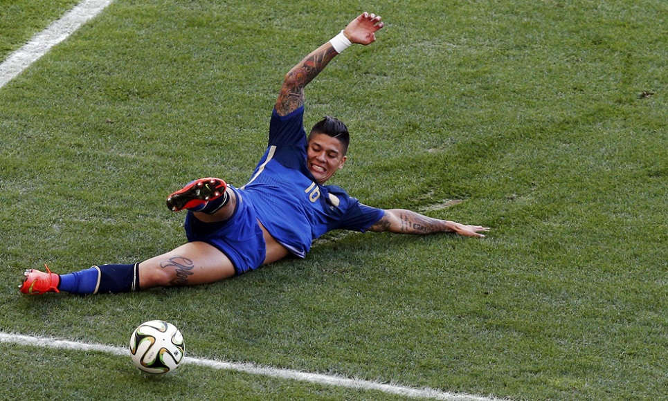 Argentina's Marcos Rojo slides for the ball during their 2014 World Cup final against Germany at the Maracana stadium in Rio de Janeiro