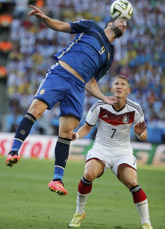 Argentina's Higuain jumps for the ball with Germany's Schweinsteiger during their 2014 World Cup final at the Maracana stadium in Rio de Janeiro