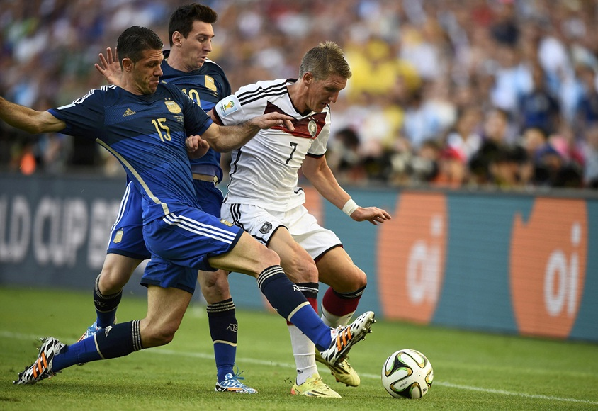 Germany's Schweinsteiger is challenged for the ball by Argentina's Demichelis and Messi during their 2014 World Cup final at the Maracana stadium in Rio de Janeiro