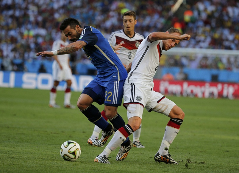 Argentina's Lavezzi fights for the ball with Germany's Hoewedes during their 2014 World Cup final at the Maracana stadium in Rio de Janeiro
