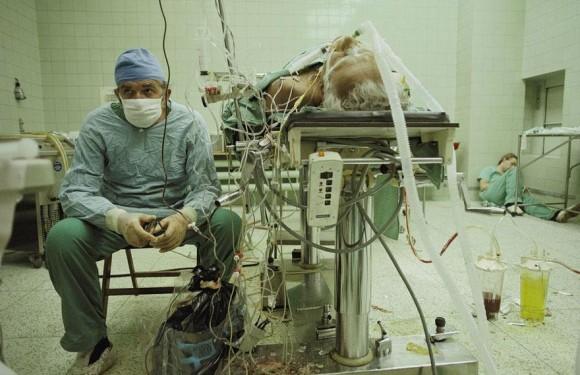 Un cirujano cardíaco después de una cirugía exitosa de un trasplante de corazón que se llevó a cabo en 23 horas. Su asistente está durmiendo en el rincón.