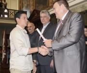 El Dr. Gustavo Cobreiro (D), Rector de la Universidad de La Habana, entrega el Título de Oro a un graduado de la Facultad de Comunicación de la Universidad de La Habana, en acto el acto de graduación efectuado en el Aula Magna de ese centro de altos estudios, el 10 de julio de 2014. A su lado Miguel Díaz-Canel (C), Primer Vicepresidente de los Consejos de Estado y de Ministros.  AIN FOTO/Abel PADRÓN PADILLA