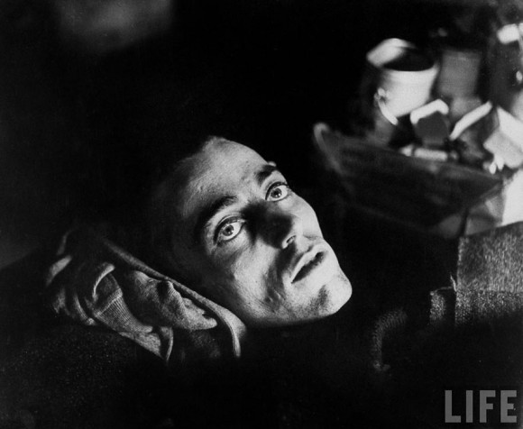Un acercamiento de la inquietante mirada de un demacrado prisionero de guerra estadounidense, mientras yace en su cama luego de ser liberado de un campo de prisioneros alemán, por parte de las fuerzas Aliadas. Tomada en Limburg, Alemania, 1945.