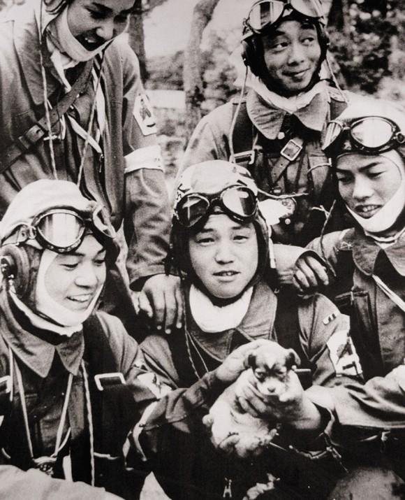 """Esta imagen muestra al cabo Yukio Araki (de 17 años de edad) sosteniendo a un cachorro junto a otros 4 jóvenes (de unos 18 años) del 72º Escuadrón Shinbu (poder militar). Un camarógrafo del periódico japonés """"Asahi Shimbun"""" tomó esta foto el día antes de la partida del 72° cuerpo del Ejército Shinbu desde la base aérea de Bansei, a sus misiones Kamikaze en Okinawa. Yukio Araki murió a la edad de 17 años y 2 meses en un ataque suicida a barcos estadounidenses cerca de Okinawa el 27 de Mayo de 1945. Casi todos los pilotos kamikazes de las fuerzas armadas durante la campaña de Okinawa, tenían entre 17 y 22 años. No es el tipo de imagen que las personas se imaginan al escuchar hablar de los pilotos kamikazes."""