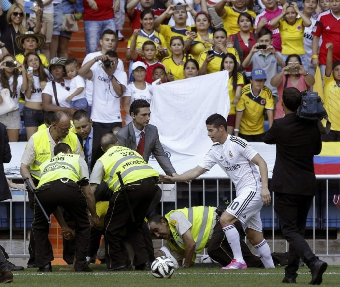 El jugador colombiano James Rodríguez se preocupa por un aficionado que ha saltado al césped y ha sido rodeado por miembros de seguridad, durante su presentación esta martes 22 de julio en el estadio Santiago Bernabéu, en Madrid. FOTO: EFE.