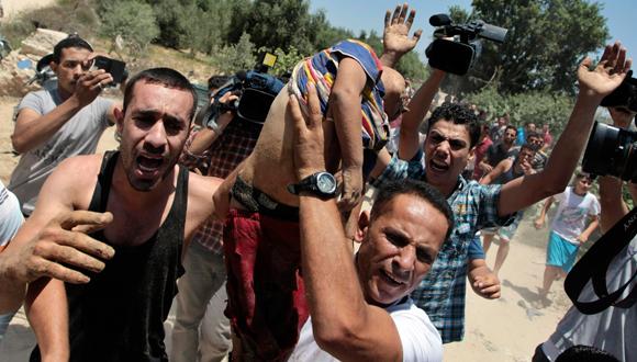 Alzan el cuerpo de un niño asesinado en uno de los 160 bombardeos lanzados por Israel. Foto: Reuters