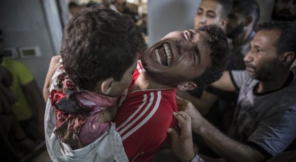 Un palestino llora mientras sostiene el cuerpo muerto de su hermano menor en la morgue del hospital al-Shifa en la ciudad de Gaza el 16 de julio. Su hermano era uno de los cuatro chicos de la familia Bakr muertos en lo que parecía ser el bombardeo naval israelí cerca de la ciudad de Gaza mientras jugaban al fútbol en la playa. Foto: EPA/ Oliver Wiken