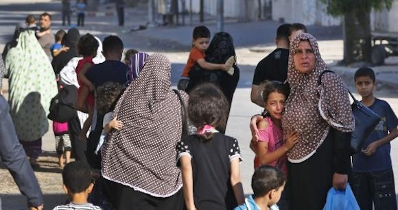 Varios palestinos huyen de sus casas en el barrio de Shuyaiya, Ciudad de Gaza, el 16 de julio. Foto: L. PITARAKIS (AP)