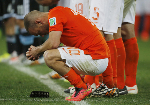 Sneijder of the Netherlands reacts after his teammate Vlaar missed an opportunity to score a goal against Argentina during a penalty shoot-out at their 2014 World Cup semi-finals at the Corinthians arena in Sao Paulo